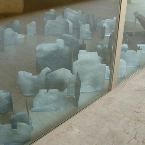 Quoi de nouveau sous le soleil? - Mobile city 1, 2005/6. Lamiera di zinco ritagliata e piegata, valigia d'alluminio. Installazione a terra, in situ.