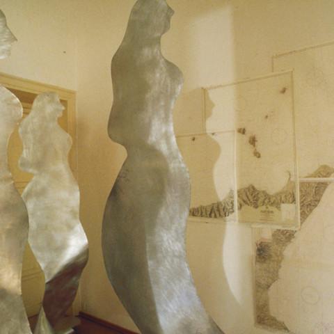 Sirene - Reflux (2001). Sagome di zinco sabbiato appese con un amo d'acciaio, fili di nylon, carte nautiche, luce artificiale (dimensioni variabili). Ph. Sandro Scalia.