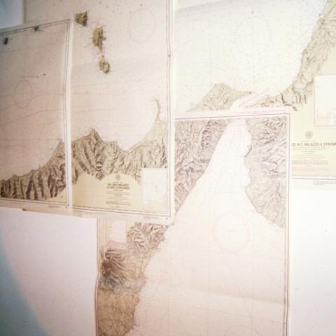 Sirene - Reflux (2001). Sagome di zinco sabbiato appese con un amo d'acciaio, fili di nylon, carte nautiche, luce artificiale (dimensioni variabili).